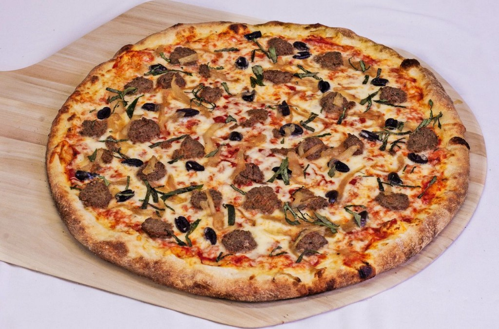 Pizza with mozzarella, meatballs, onions, olives, and basil