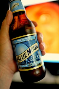 A hand holding a bottle of Blue Moon beer.